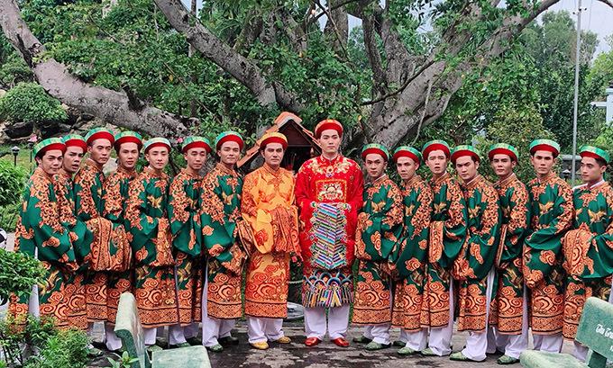 Nam diễn viên và các đồng nghiệp chụp ảnh kỷ niệm trong khuôn viên nhà thờ Tổ rợp bóng cây xanh.