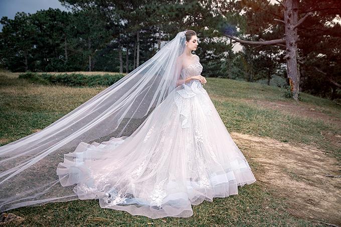 Váy xòe có độ chuyển màu ombre là một thử nghiệm mới của Anh Thư với dòng váy cưới. Chị xử lý họa tiết nơi eo tựa đoá sen nở rộ trên nền thớ vải trắng. Phần viền váy có màu xanh pastel giúp níu giữ ánh nhìn.