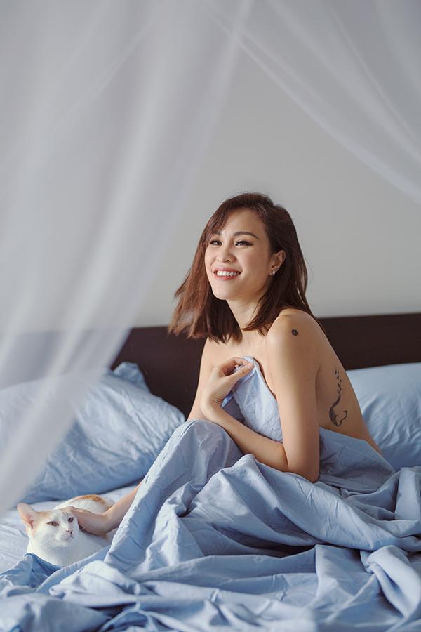 Phương Mai khoe hình xăm khi bán nude. Nữ MC che chắn những điểm nhạy cảm trên cơ thể bằng tấm chăn mỏng trong phòng ngủ của mình.