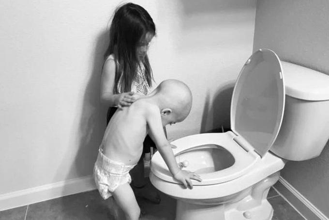 Bức ảnh Aubrey chăm sóc e trai trong nhà vệ sinh được mẹ chia sẻ trên mạng xã hội. Ảnh: The Sun.