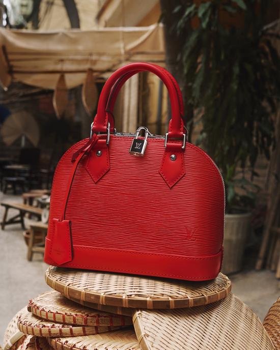 Túi Alma BB tông màu đỏ tươi của Louis Vuitton nổi bật trên nền các vật dụng mây tre đan lát của Việt Nam.