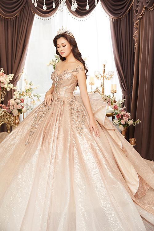 Để tạo sự mới lạ cho mẫu đầm cổ điển, NTK Anh Thư không chọn gam màu trắng tinh khôi mà sử dụng màu ombre. Đằng sau váy là họa tiết nơ xếp nếp, giúp cô dâu níu giữ ánh nhìn của khách mời.