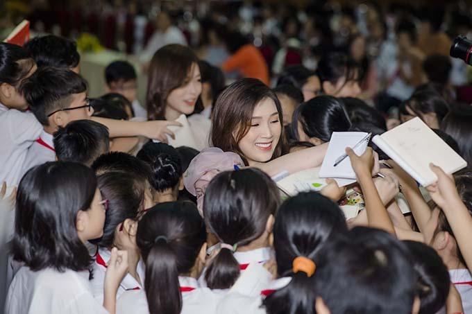 Phí Thuỳ Linh lọt thỏm trong vòng vây của fan nhí. Cô cảm thấy rất hạnh phúc vì được nhiều bạn học sinh yêu mến.