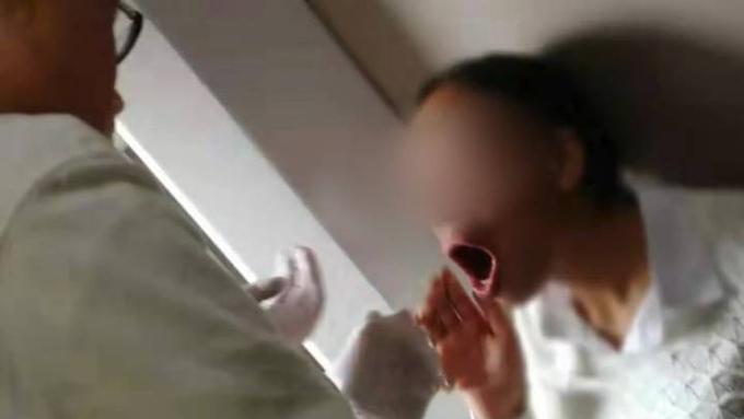 Bác sĩ Luo Wensheng giúp người phụ nữ nắnlại hàm sái trên chuyến tàu hôm 1/9. Ảnh: OC.