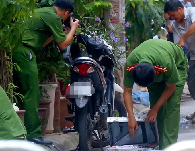 Công an khám nghiệm chiếc xe máy của nam thanh niên gây án để ở trước cửa ngôi nhà xảy ra án mạng. Ảnh:Phương Sơn.