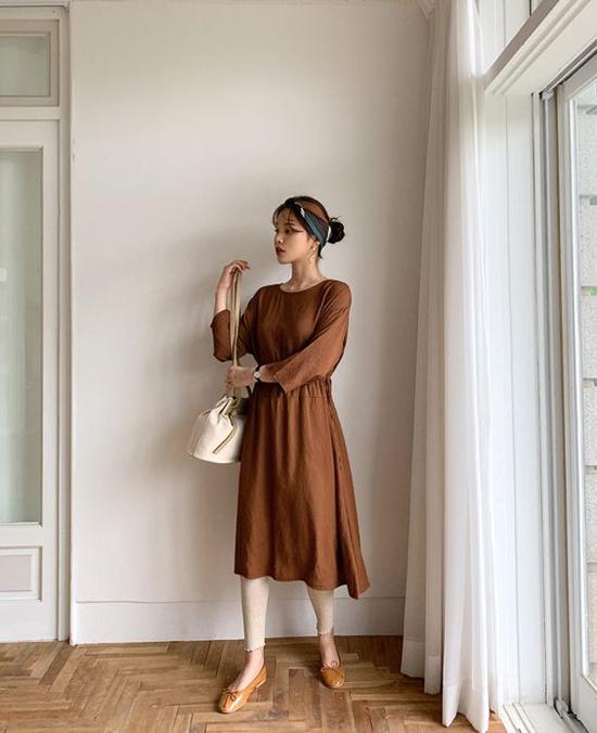Set đồ đúng chất mùa thu với cách kết hợp giữa váy thắt eo tông nâu, giầy búp bê đồng điệu màu sắc. Phụ kiện đi kèm là khăn turban, túi rút dây vải bố.
