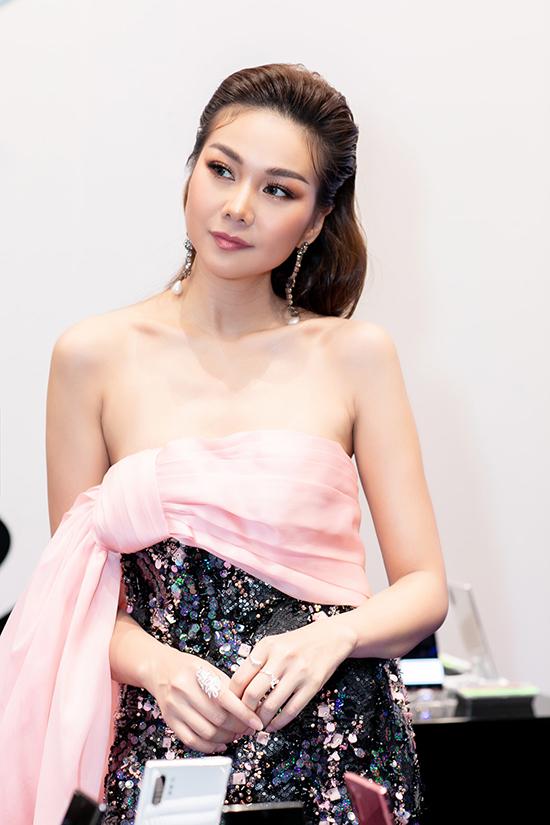 Siêu mẫu Thanh Hằng khoe vai trần trong thiết kế váy sequins. Đầm dạ hội cúp ngực được nhà mốt Việt tạo ấn tượng bằng cách phối dải lụa hồng vòng quanh phần ngực.