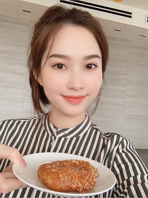 Đặng Thu Thảo cột tóc cao, không trang điểm cầu kỳ khi pose hình cùng món bánh cam yêu thích. Nhan sắc đời thường của Hoa hậu Việt Nam 2012 được fan khen trẻ và xinh đẹp hơn.