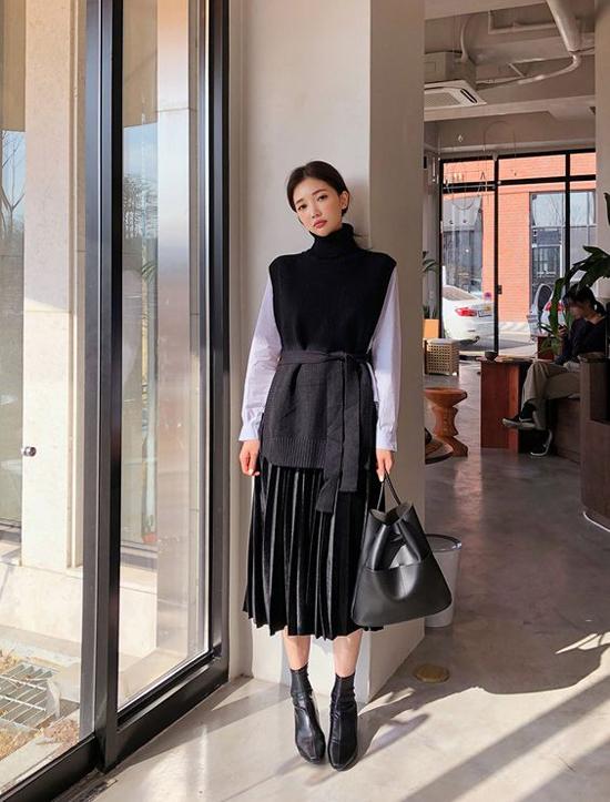 Cách phối màu trắng đen hoàn hảo cho set đồ gồm áo cổ lọ, áo len, chân váy xếp ly, bốt cổ thấp và túi da ton-sur-ton.