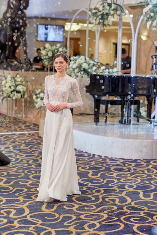 Váy ren lấy cảm hứng từ trang phục của cô dâu hoàng gia châu Âu mang đến sự sang trọng, cổ điển. Bộ đầm có dáng suông đơn giản, thân váy trơn, giúp nàng dễ dàng sải bước trong hội trường cưới.