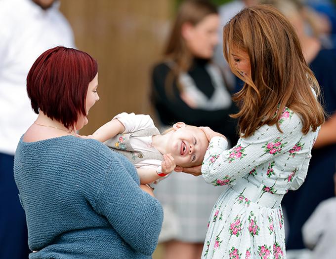 Kate vui đùa với một em bé 15 tháng tuổi khi khai trương vườn thiên nhiên hôm 10/9. Ảnh: PA.