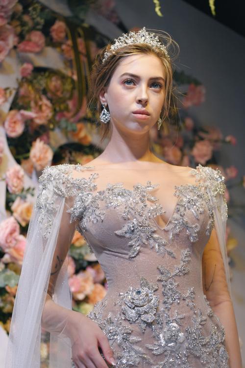 NTK chọn lựa kiểu cổ illusion, tà phụ bắt đầu từ cầu vai để tạo sự đặc sắc cho thiết kế. Họa tiết hoa hồng lấp lánh được điểm lên thân váy, tạo hiệu ứng sân khấu, giúp nàng nổi bật ở đêm tiệc của mình.
