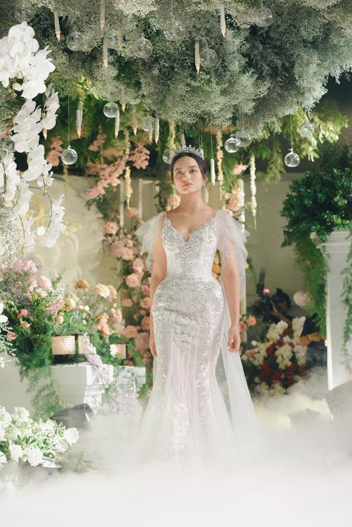 Váy cưới tay cánh tiên là một sáng tạo dành cho cô dâu ưa chuộng sự nữ tính, điệu đà. Váy không kén dáng, giúp nàng che giấu bắp tay kém thon. Trên nền vải trắng là họa tiết lấy cảm hứng hoàng gia châu Âu, giúp tân nương có vẻ đẹp sang trọng.