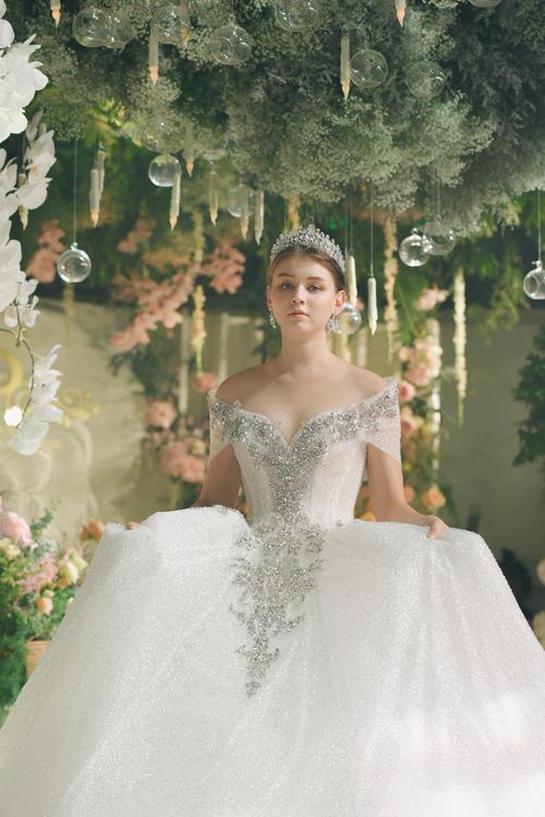 Váy xòe phồng trễ vai sinh ra là để hiện thực hóa ước mơ thành công chúa cổ tích của cô dâu từ tấm bé. Mẫu đầm được làm từ chất liệu vải kim sa cao cấp, tạo hiệu ứng bắt sáng.