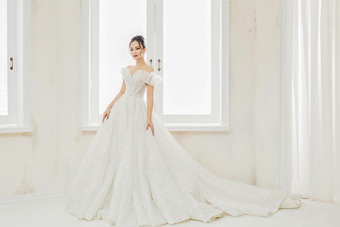 NTK Linh Nga áp dụng thế mạnh của mình là dựng gọng corset, siết eo của tân nương tới 10 cm. Phần vai trễ bồng bềnh giúp cô dâu chạm tay tới giấc mơ hóa thành công chúa cổ tích.
