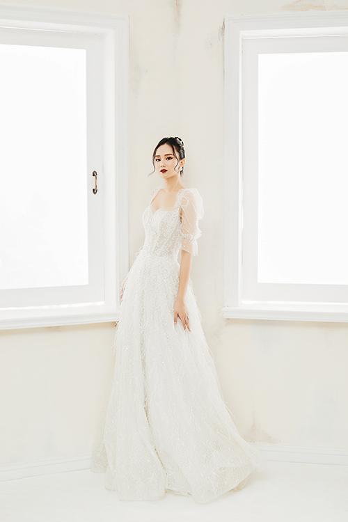 Váy cưới có cổ vuông tim, tạo hình khuôn ngực dáng giọt lệ, gợi nhắc đến bộ đầm cưới của công chúa hoàng gia châu Âu. Váy được điểm pha lê Swarovski, đá lấp lánh và lông vũ.