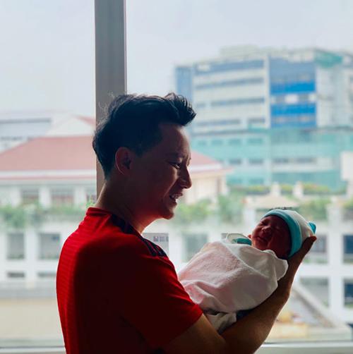 Ca sĩ Hoàng Bách đăng ảnh rõ mặt con trai thứ 3 mới sinh cách đây vài ngày. Anh cho biết đây là bình mình đầu tiên của bố và con.