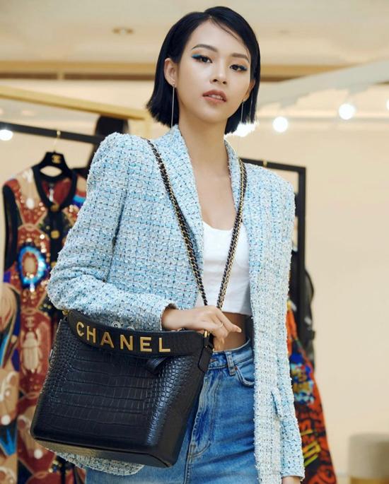 Phí Phương Anh chọn mẫu túi đắt hàng của Chanel để mix cùng áo khoác vải tweed, jeans xanh cổ điển và áo hở eo tông trắng.