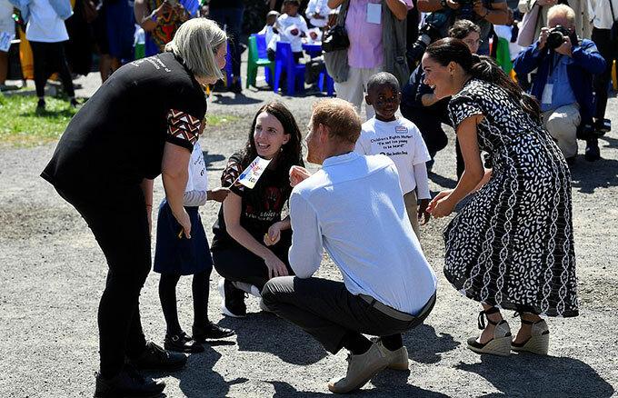 Vợ chồng Harry - Meghan không ngại ngồi xổm để trò chuyện với trẻ em Nyanga.