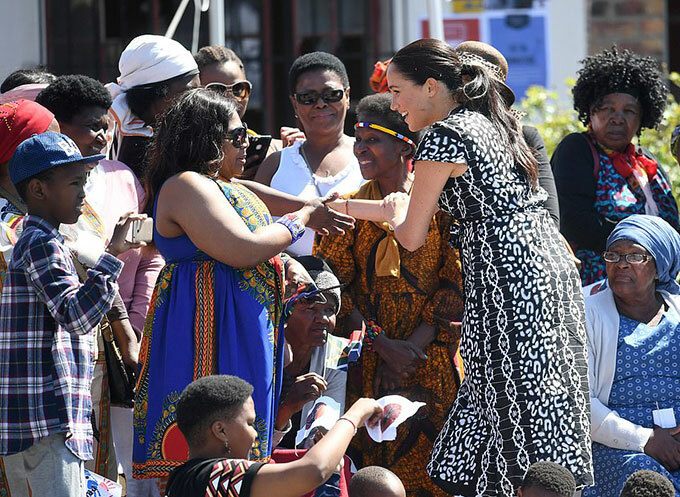Adorable moment a shy young schoolboy gives Meghan Markle a huge hug as she and Prince Harry tour township dubbed South Africas murder capital while baby Archie stays behind with a nanny amid super-tight security - 6