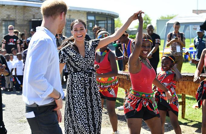 Meghan nhảy múa với một cô gái thuộc cộng đồng ở thị trấn Nyanga, ngoại ô Cape Town chiều 23/8. Ảnh: Rex.