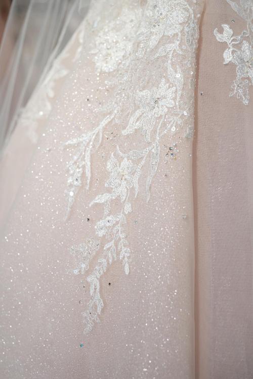 Thay vì đính kế cầu kỳ, NTK sử dụng loại vải đặc biệt mà bản thân nó có độ bắt sáng để tạo nét lung linh, huyền ảo cho cô dâu khi bước đi dưới ánh đèn sân khấu.