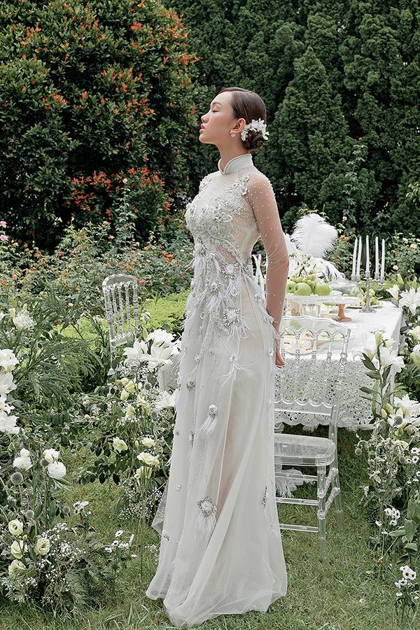 Người mẫu Thu Huyền gợi ý kiểu tóc búi thấp cài hoa điệu đà khi diện áo dài cưới.