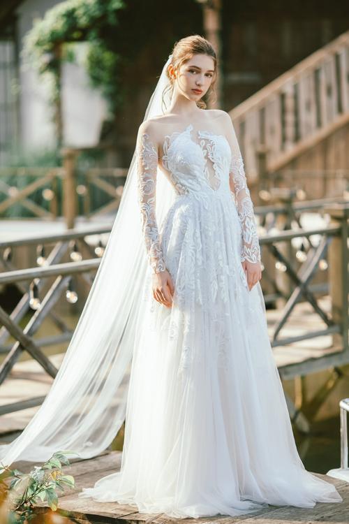 Váy Zelane là sự lựa chọn dành cho cô dâu chuộng sự lãng mạn. Thiết kế có tạo hình cúp ngực cầu kỳ, có phần thêu ren tinh tế. Váy có tùng A xòe được làm từ vải tulle mềm mại.
