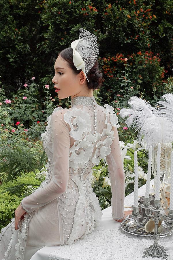 Áo dài cưới của Kenny Thái là sự pha trộn của phong cách Á - Âu khi kết hợp ren lưới, voan, organza, lông vũ với những đường cắt cúp và kỹ thuật đính kết tinh sảo để tôn lên đường cong gợi cảm của cô dâu.