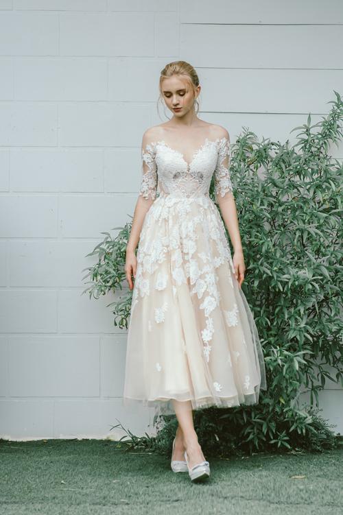 Váy Lynn là gợi ý cho cô dâu khi tìm váy cho đám cưới sân vườn hoặc đi chào bàn. Đầm màu kem có họa tiết ren thêu nổi toàn bộ thân.