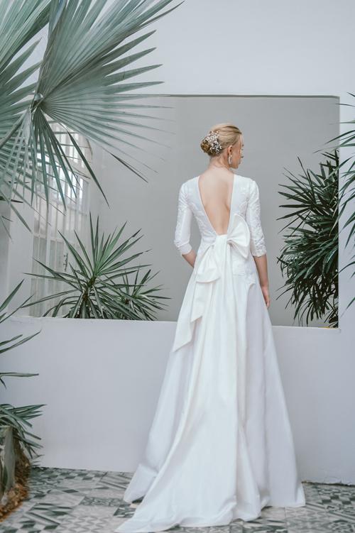 Váy Doris có tay lỡ, chất liệu taffeta tạo độ phồng tự nhiên khi diện. NTK tạo đường cắt chữ V sau lưng, nhấn nhá bằng chiếc nơ to bản cài lệch.