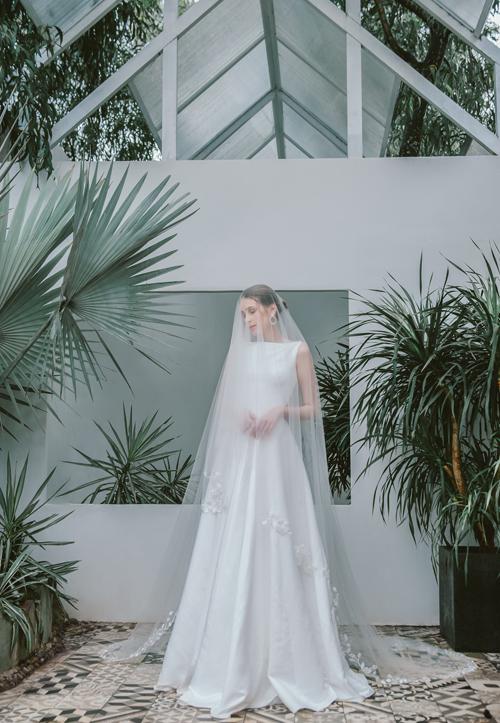 Từ chất liệu crepe đứng, váy trắng ivory tên Anita thêm sang trọng với phom dáng phồng xòe chữ A, có độ ôm dáng.