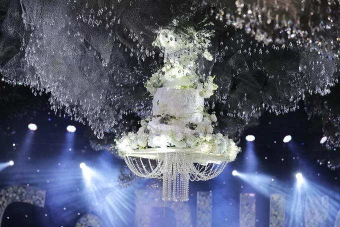 Chiếc bánh có chiều cao khoảng hai mét, đường kính lớn, choán gần hết khu vực sân khấu trang trí bằng kính và hoa. Bánh cưới của cặp sao mang sắc trắng chủ đạo, được trang trí thêm bằng hoa và những sợi dây pha lê lấp lánh. Ở các góc chụp khác nhau, chiếc bánh đều nổi bật trên nền đám mây được kết từ pha lê.