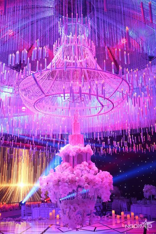 Chiếc bánh cùng dàn đèn chùm pha lê và 10.000 ngọn nến trắng giúp không gian trở nên lãng mạn, lung linh hơn trong tiệc tối.