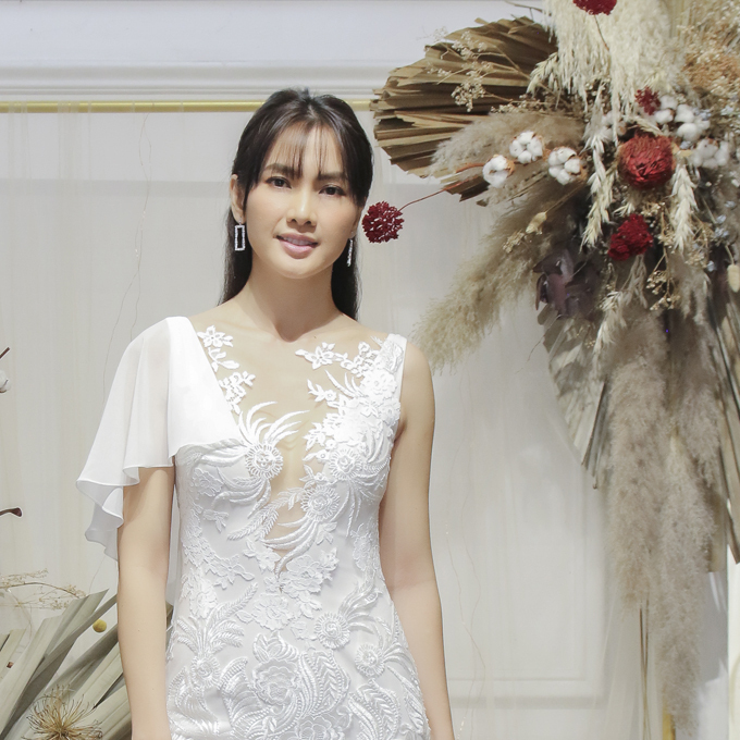 Anh Thư diện thêm váy có cổ chữ V xẻ ngực sâu kết hợp voan mỏng. Điểm nhấn của váy không chỉ nằm ở thiết kế cổ áo mà còn ở phần vai bất đối xứng, dành cho cô dâu yêu thích sự mới lạ.
