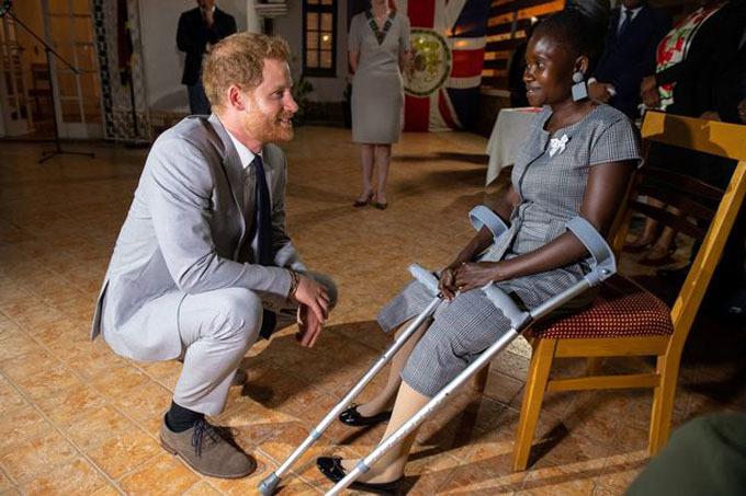 Harry ngồi hẳn xuống để nói chuyện với Sandra trong ngày thứ hai anh tới Angola. Ảnh: Reuters.