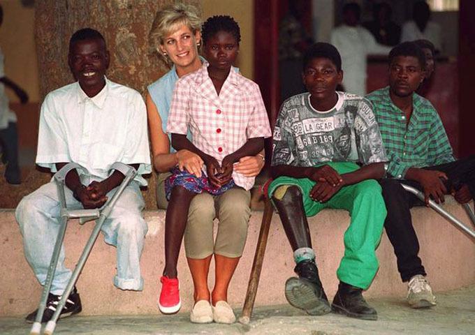 Sandra ngồi trên chân Diana trong chuyến thăm của bà tới trung tâm các nạn nhân bị thương tật vì bom mìn năm 1997. Ảnh: Tim Graham.