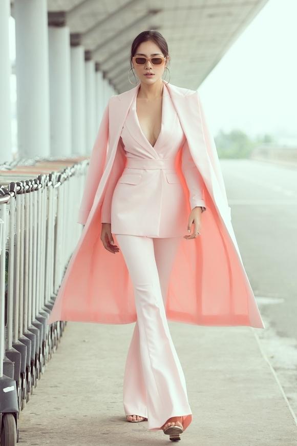Chân dài 27 tuổi sải bước ở sân bay với vest hồng pastel, áo choàng rộng khoét sâu ngực khoe vòng 1 gợi cảm.