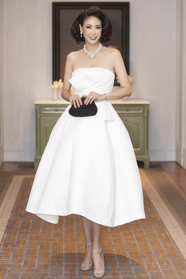 Hoa hậu Việt Nam 1992 Hà Kiều Anh diện váy trắng xoè cúp ngực với điểm nhấn ở chi tiết nơ to bản.