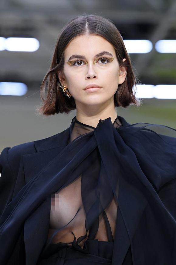Kaia trình diễn set đồ đen với vest suông rộng mặc ngoài sơ mi xuyên thấu. Trong quá trình sải bước, vạt áo vest chuyển động khiến cô không may bị lộ trọn vẹn một bên ngực.