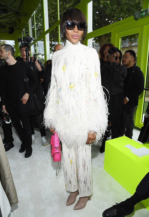 Show Valentino quy tụ nhiều khách mời nổi tiếng, trong đó có cựu siêu mẫu Naomi Campbell. Báo đen chọn trang phục gam trắng chủ đạo, nhấn nhá chi tiết tua rua mềm mại và kết hợp clutch hồng neon nổi bật.