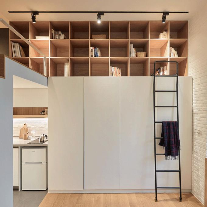 Ở không gian sinh hoạt chung có một tủ quần áo, tủ vuông đựng sách kéo dài 3,3 m từ sàn tới trần nhà. Khi muốn đọc sách, gia chủ có thể dùng thang để lấy sách trên cao.