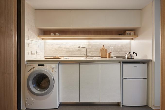 Khu vực bếp có đầy đủ tiện nghi, tủ lạnh, máy giặt được đặt dưới kệ bếp.