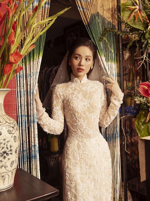 Áo dài ren trắng mang phom dáng truyền thống nhưng có độ ôm, giúp tôn vóc dáng của tân nương.