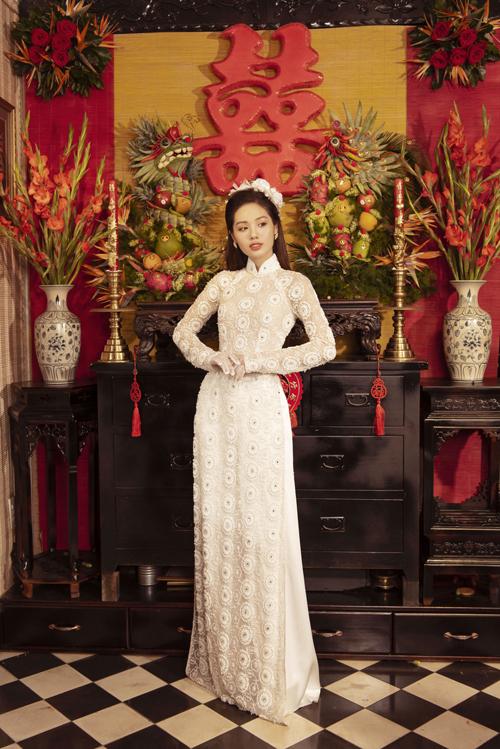 Áo dài trắng có họa tiết tròn dọc thân làm điểm nhấn.