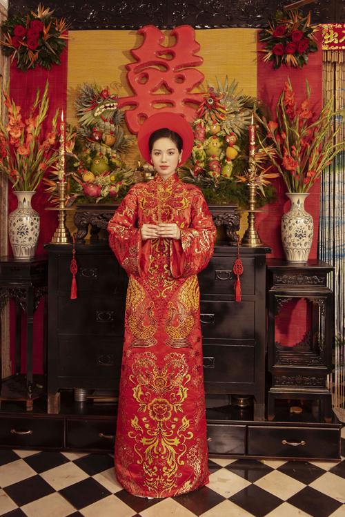 Áo dài đỏ rực rỡ có họa tiết truyền thống đối xứng làm điểm nhấn. NTK Bảo Bảo chọn lựa sắc vàng đồng để họa tiết nổi trên nền áo đỏ.