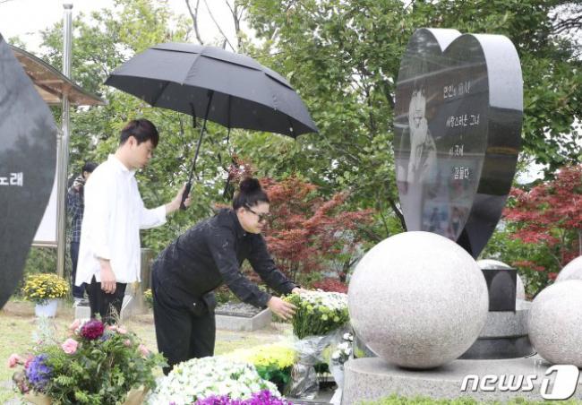 Trời lất phất mưa khi Lee Jung Jae đến đặt hoa viếng bạn.