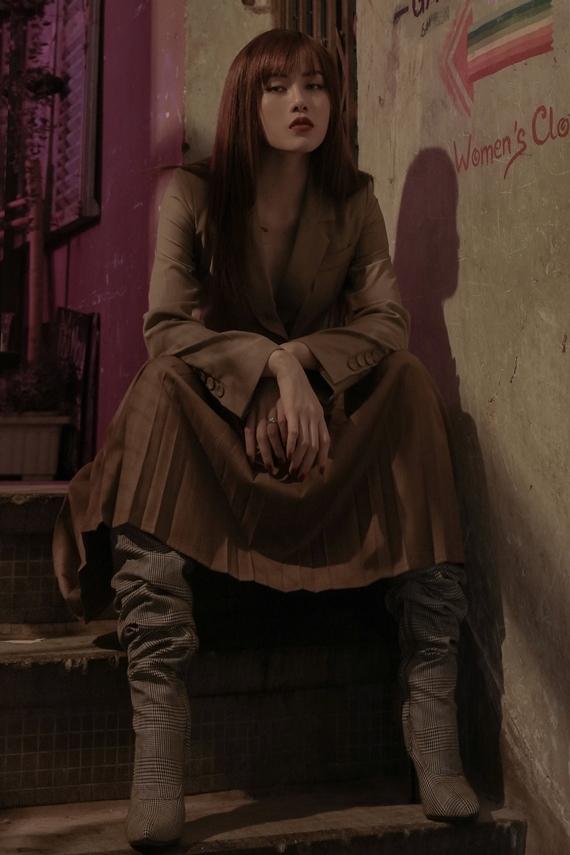 Ca sĩ sinh năm 1994 gợi ý vest xẻ ngực cùng chân váy xếp ly. Trang phục tông nâu trầm thích hợp chưng diện vào mùa thu.