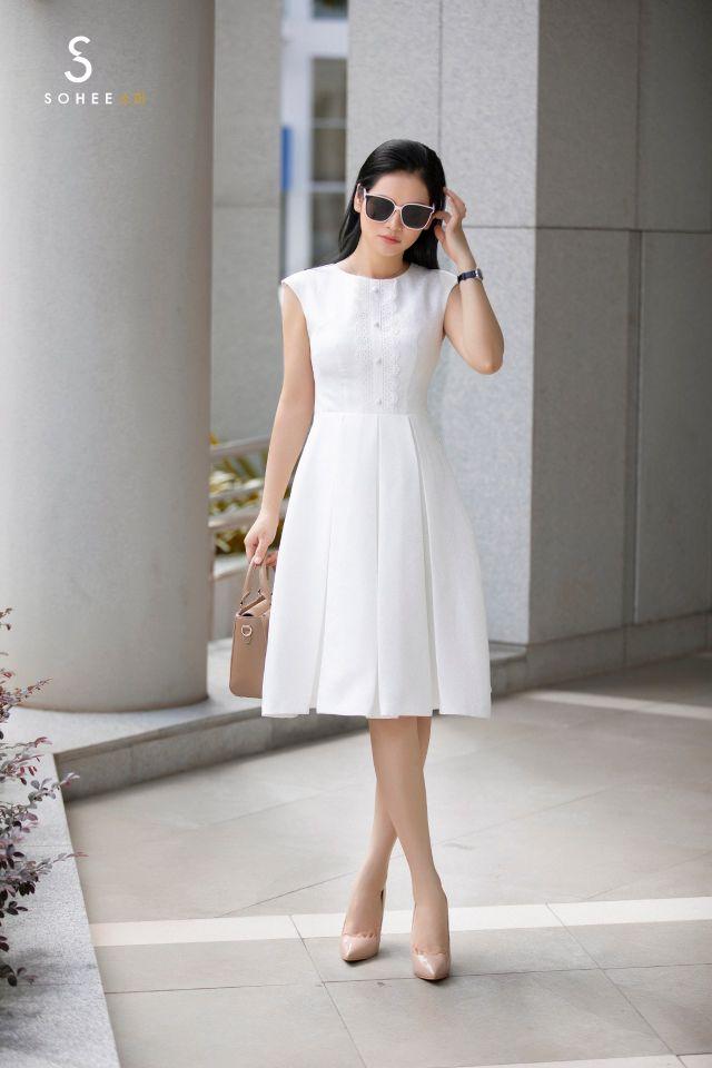Thiết kế đầm trắng chữ A với đường xếp ly mang hơi hướng cổ điển nhưng có nét hiện đại nhờ chi tiết hàng cúc đính trên thân váy. Bộ cánh tôn vóc dáng, giúp phái đẹp che bớt khuyết điểm ở vòng eo.