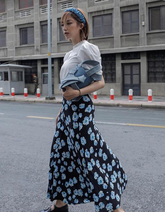 Salim bỗng dịu dàng và nữ tính hơn hẳn ngày thường khi xuất hiện trên phố Sài Gòn với áo tay bồng và chân váy hoa. Đây là set đồ không kén dáng và dễ áp dụng cho các nàng công sở khi đi làm hoặc dạo phố.